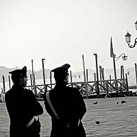 twopolicemen - Early morning on St Marks Square, Venice, Italy. Two policeman stand taking in the beautiful Venetian Summer morning.  -  photograph for sale